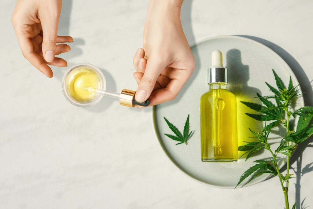 Pipette with CBD cosmetic oil in female hands with bottle of cannabis oil and hemp leaves, marijuana